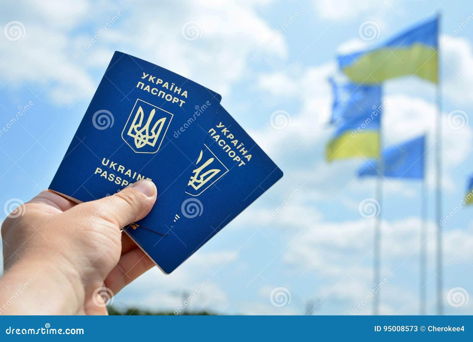 Passaporte biométrico azul ucraniano novo com microplaqueta da identificação sobre contra o céu azul e o fundo de ondulação da ba