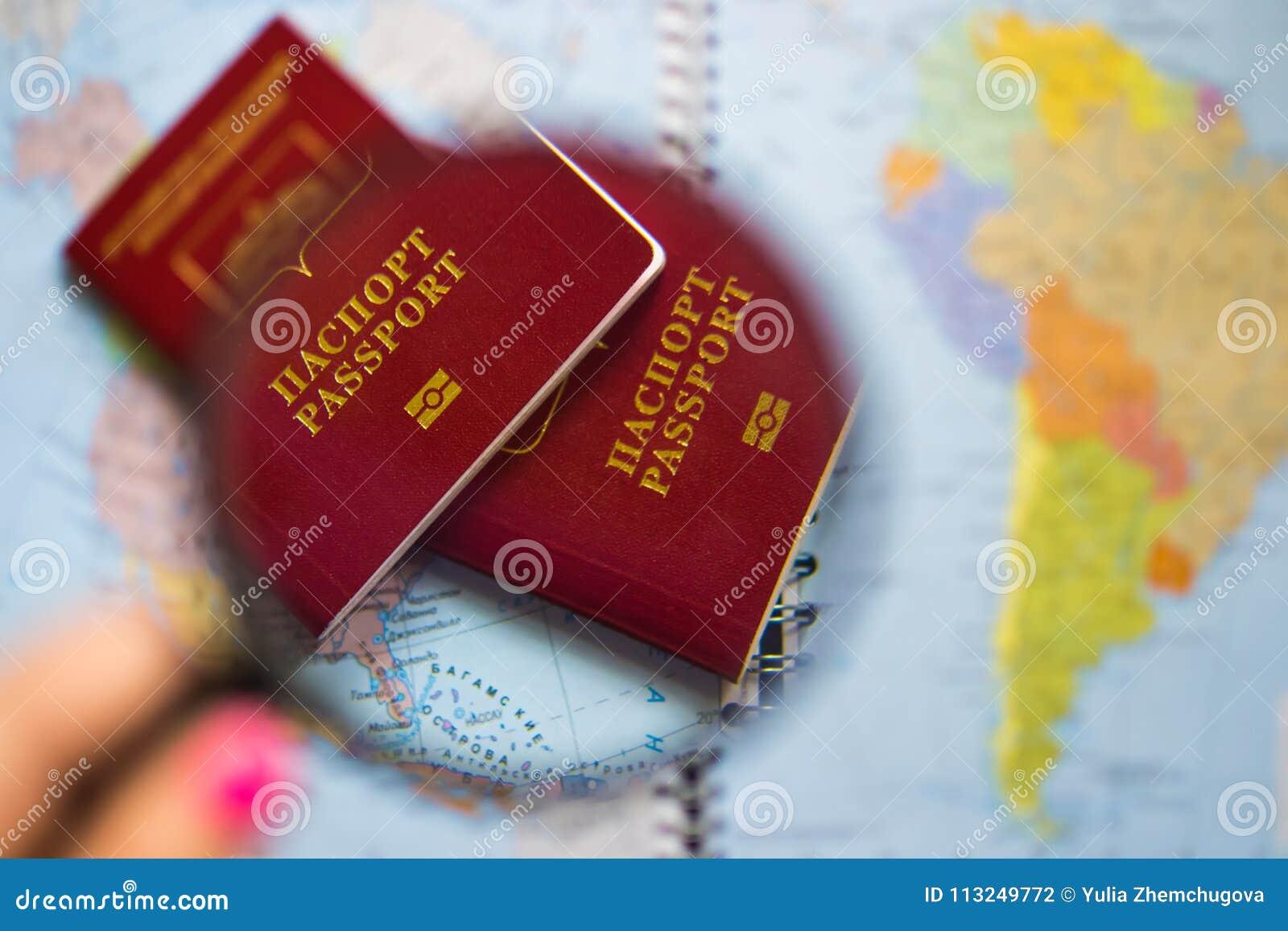 Passaporto sotto il vetro della lente d ingrandimento sulla mappa del fondo del mondo