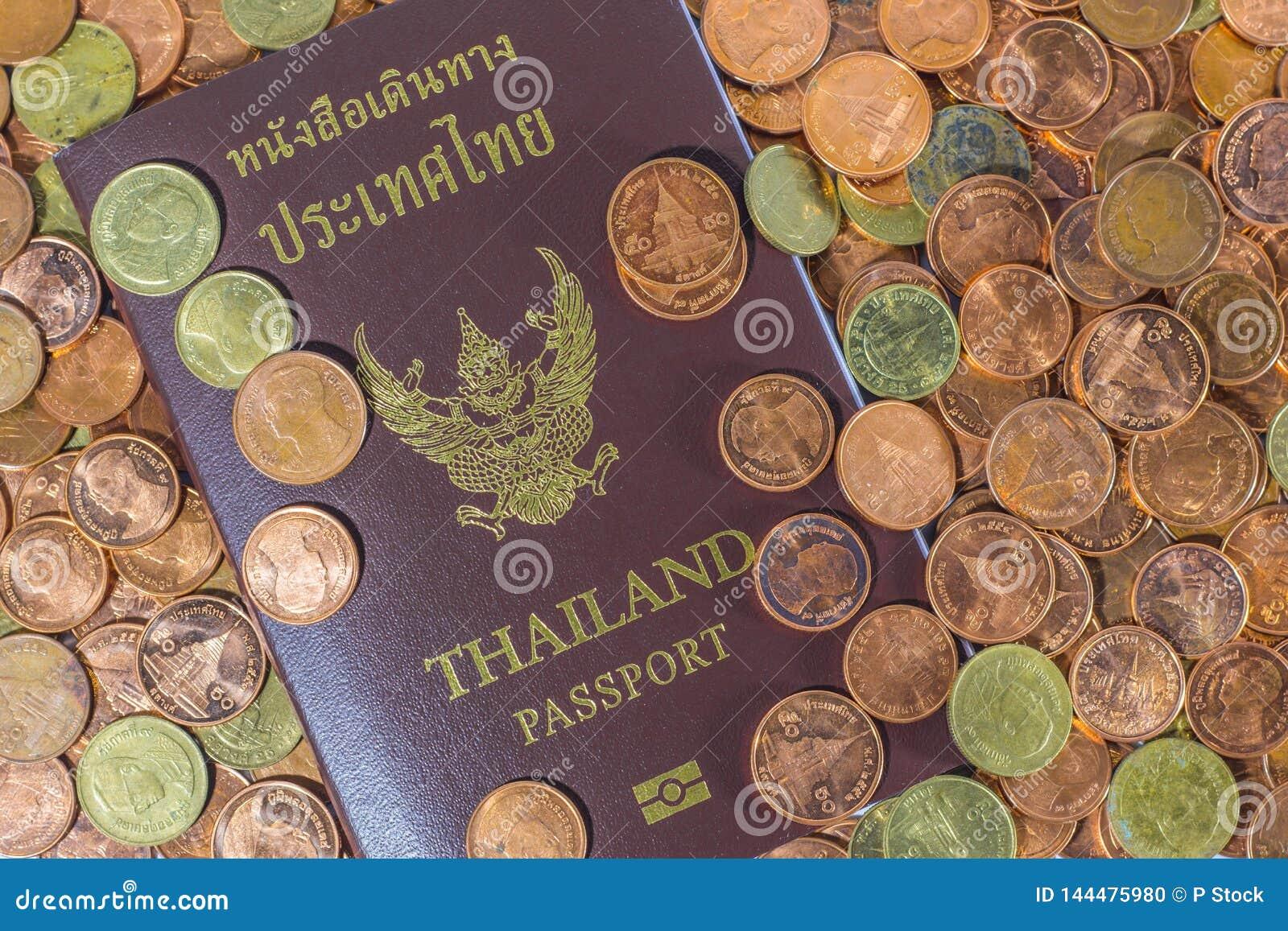 Passaporto tailandese su un mucchio delle monete