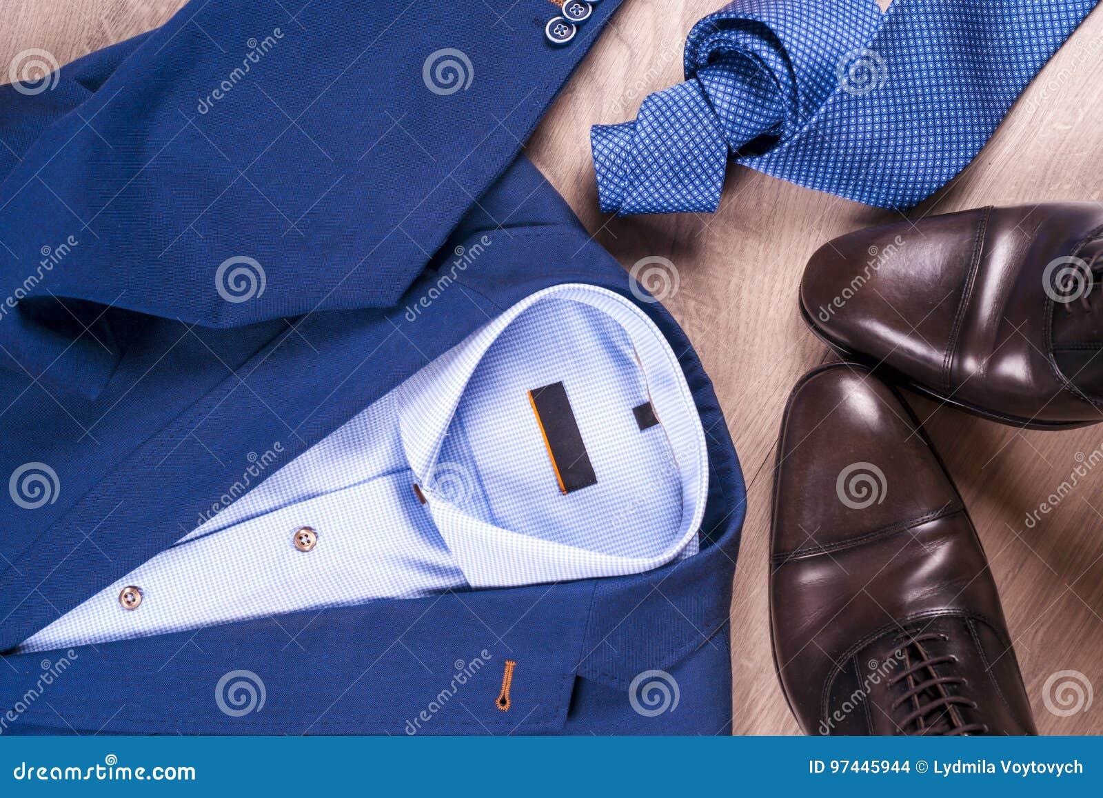 Passar den lekmanna- uppsättningen för lägenheten av klassiska mäns kläder liksom blått, skjortor, bruntskor, bältet och bandet p