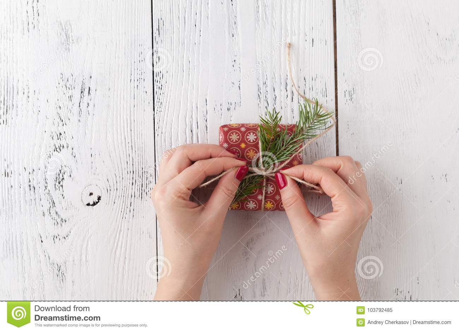 Passatempo criativo As mãos do ` s da mulher envolvem o presente feito a mão do feriado do Natal no papel do ofício com fita da g