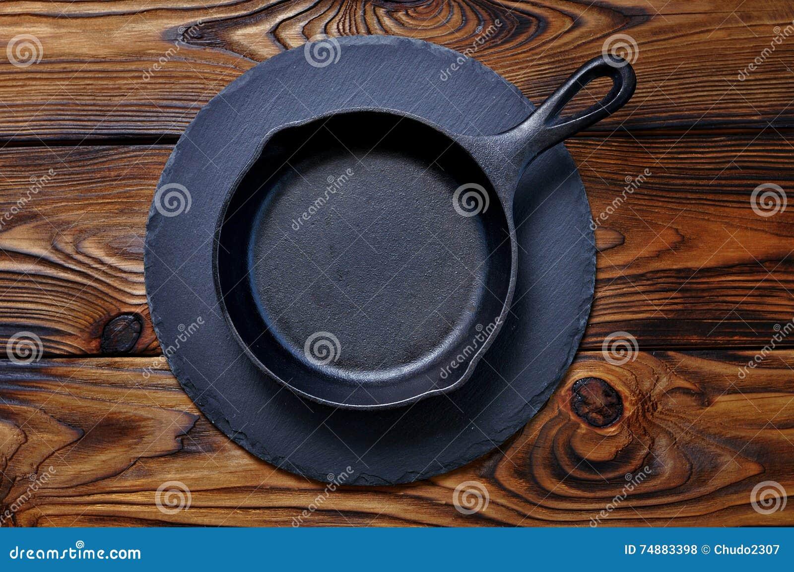 Passe a frigideira em uma placa do serviço no fundo de madeira
