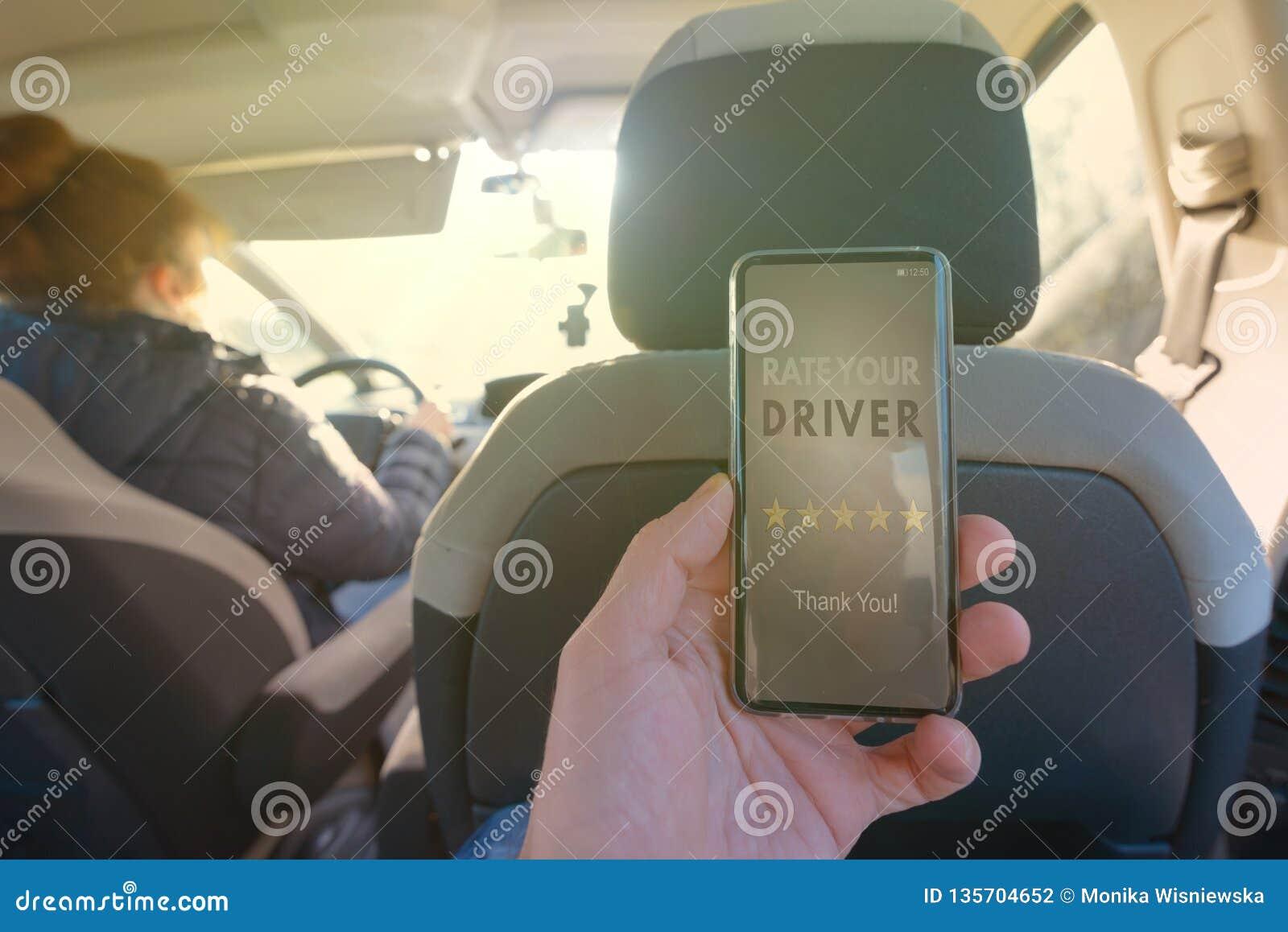 Passeggero che per mezzo del app dello Smart Phone per valutare un taxi o un autista ridesharing peer-to-peer moderno