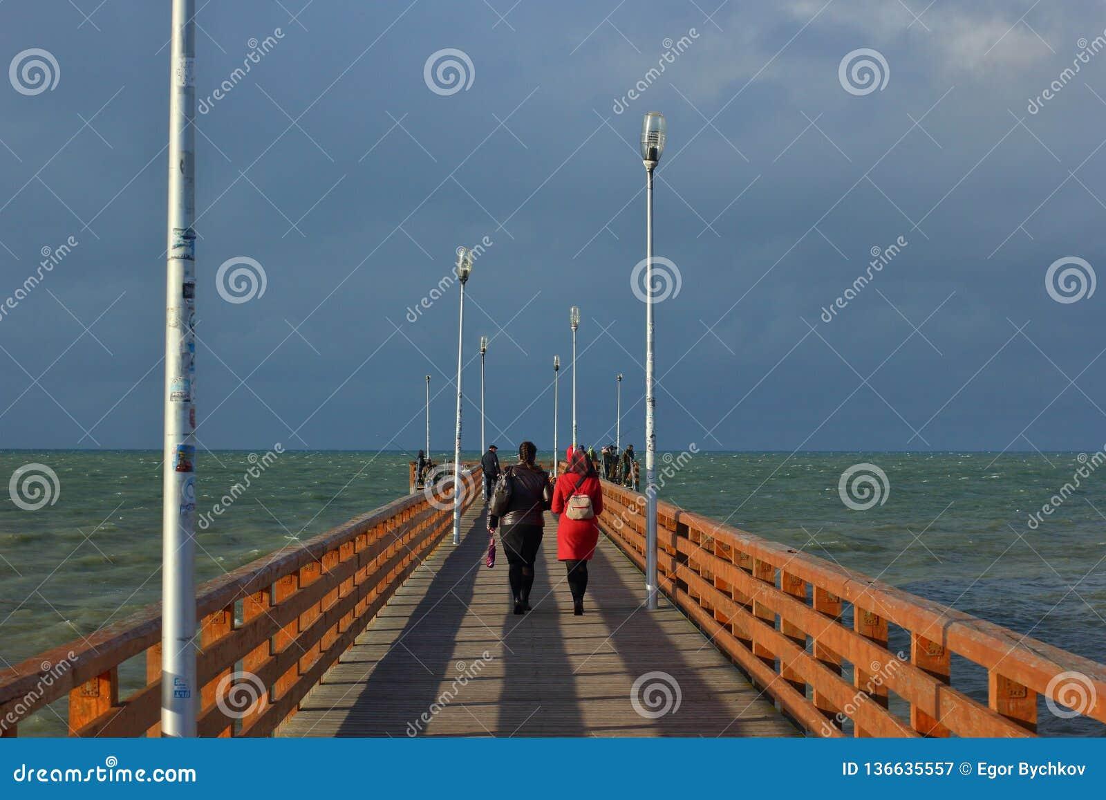 Passeio à beira mar de madeira ao mar no dia nebuloso