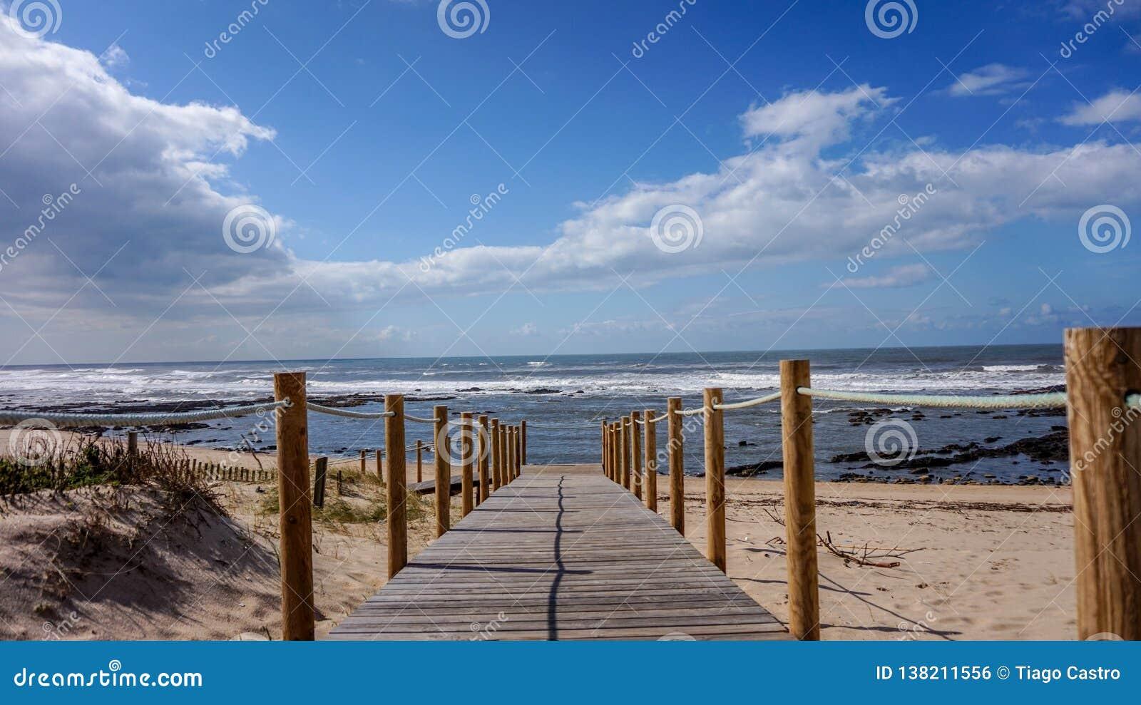 Passeio à beira mar sobre as dunas de areia que conduzem ao mar em uma manhã bonita e relaxando da praia em Gaia, Porto, Portugal