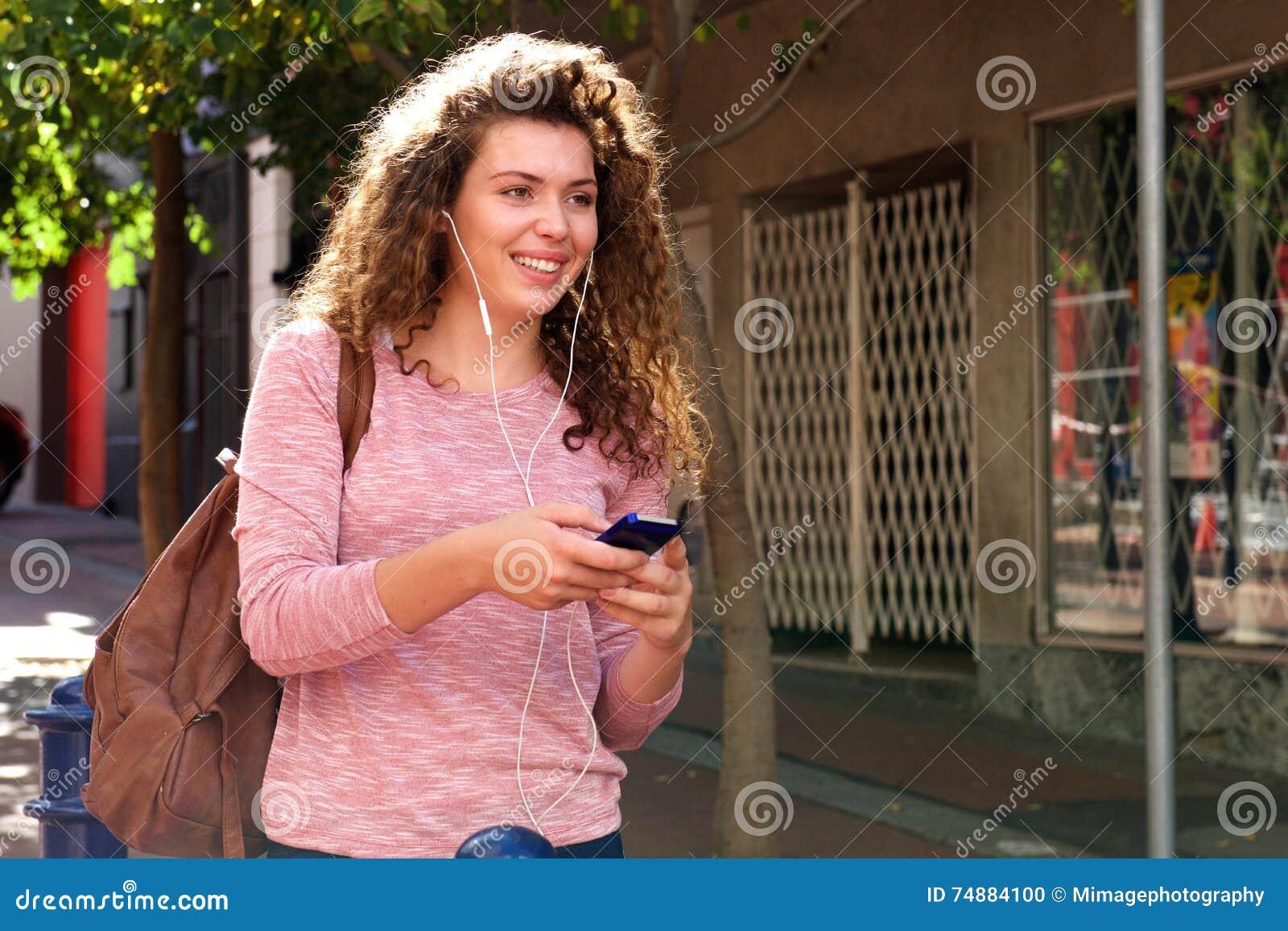 Passeio adolescente feliz no passeio com fones de ouvido e móbil