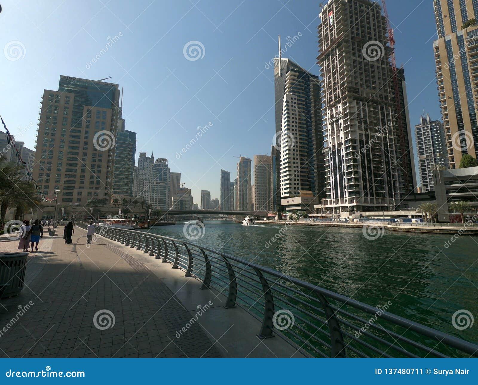 Passeio de passeio no porto de Dubai com vista da skyline, das construções e do iate