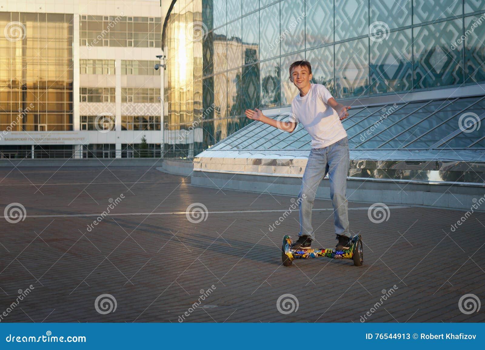 Passeios adolescentes um gyroscooter, com um sorriso e umas emoções positivas
