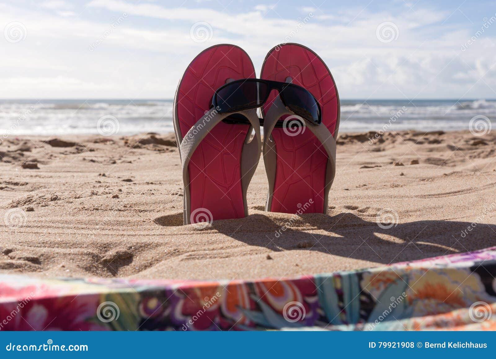 Passen Sie Flipflops mit Sonnenbrille im Sand des Strandes zusammen