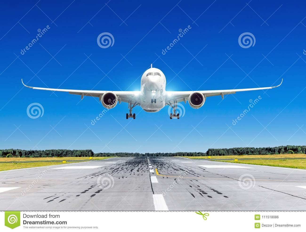 Passenger airplane with bright landing lights landing at in good clear weather with a blue sky on a runway.