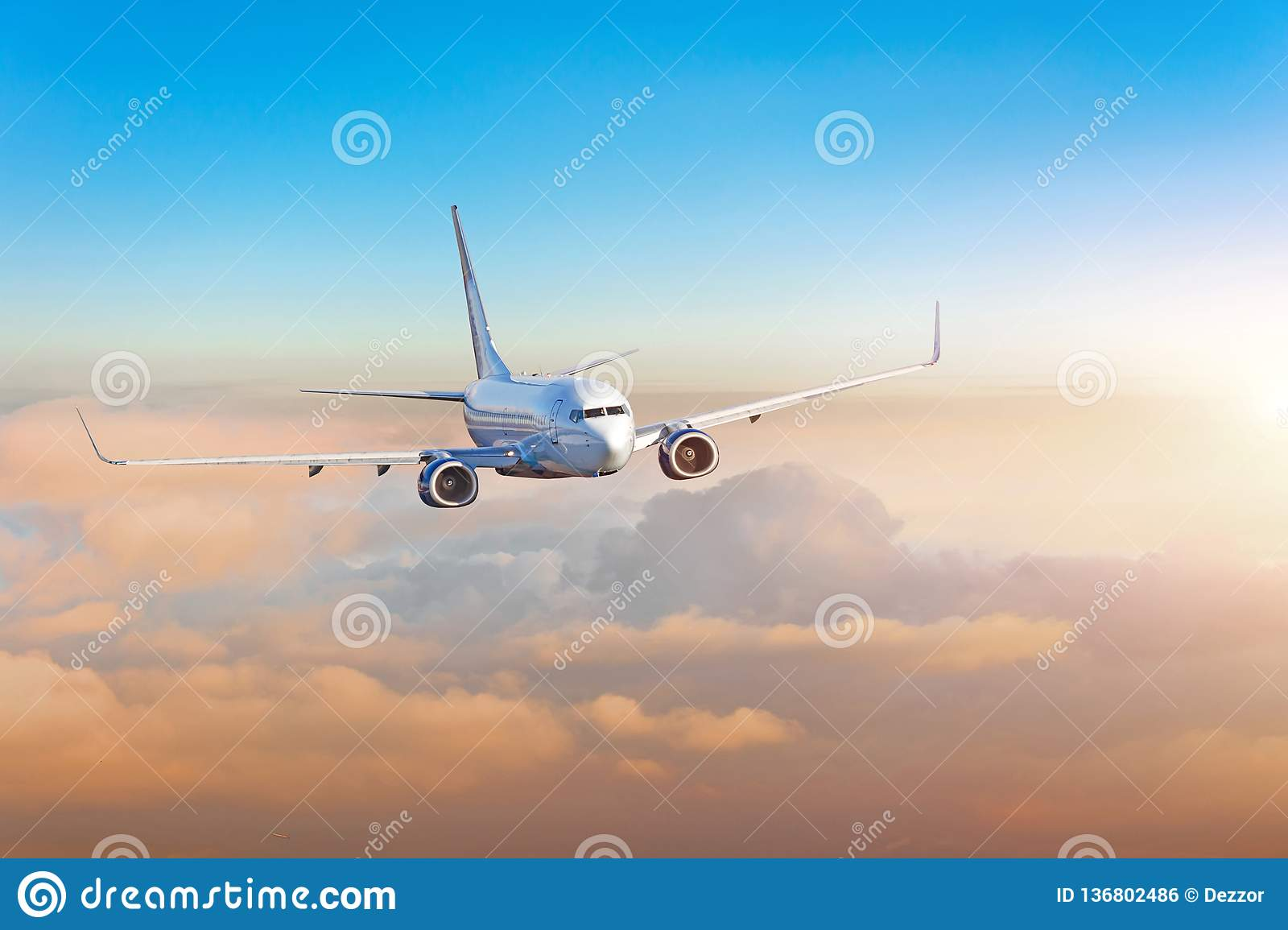 Passenger airplane, business trip, travel concept. Flying evening colorful sunset