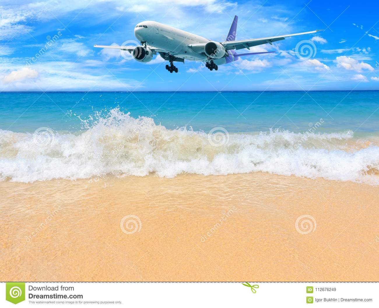 Passenger airplane flying above tropical beach in Phuket, Thailand. Amazing view of blue sea and golden sand.