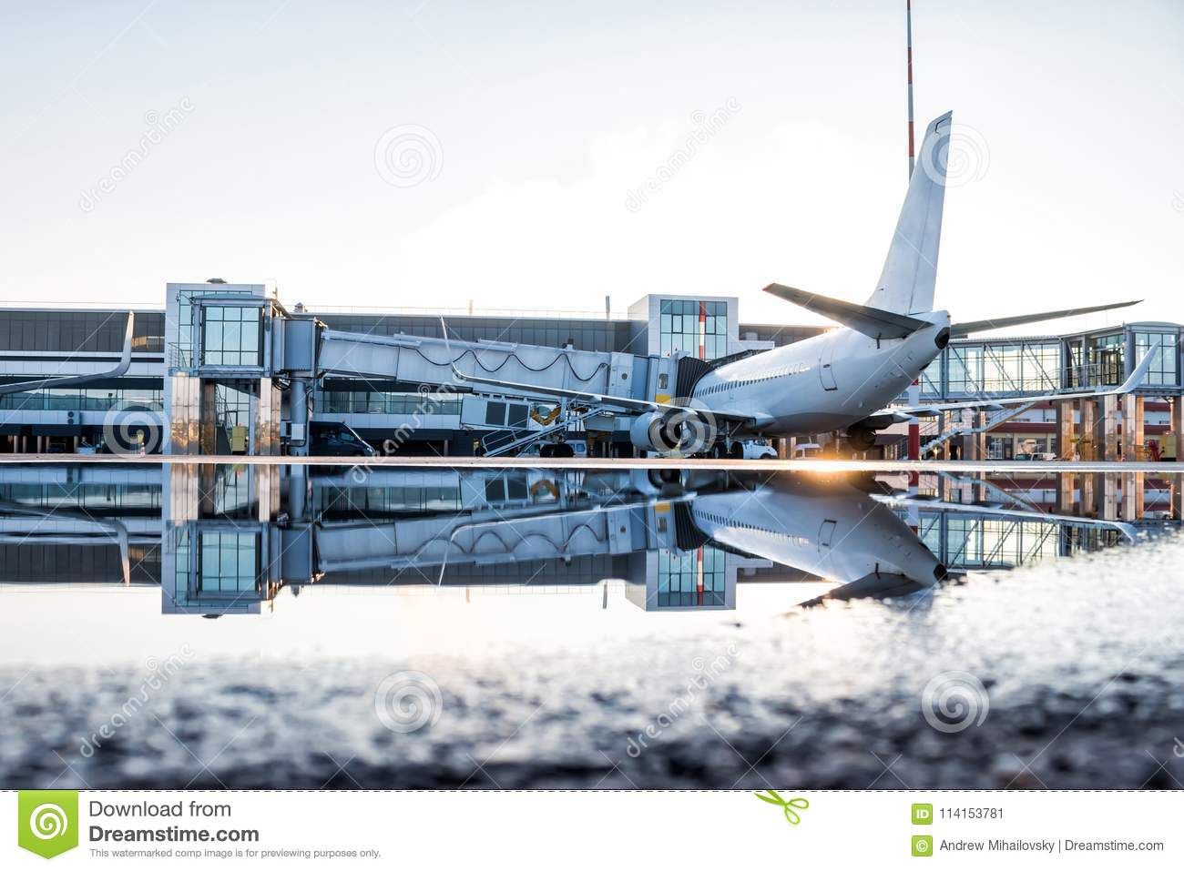 Passenger airplane parked to a air bridge with reflection in a puddle