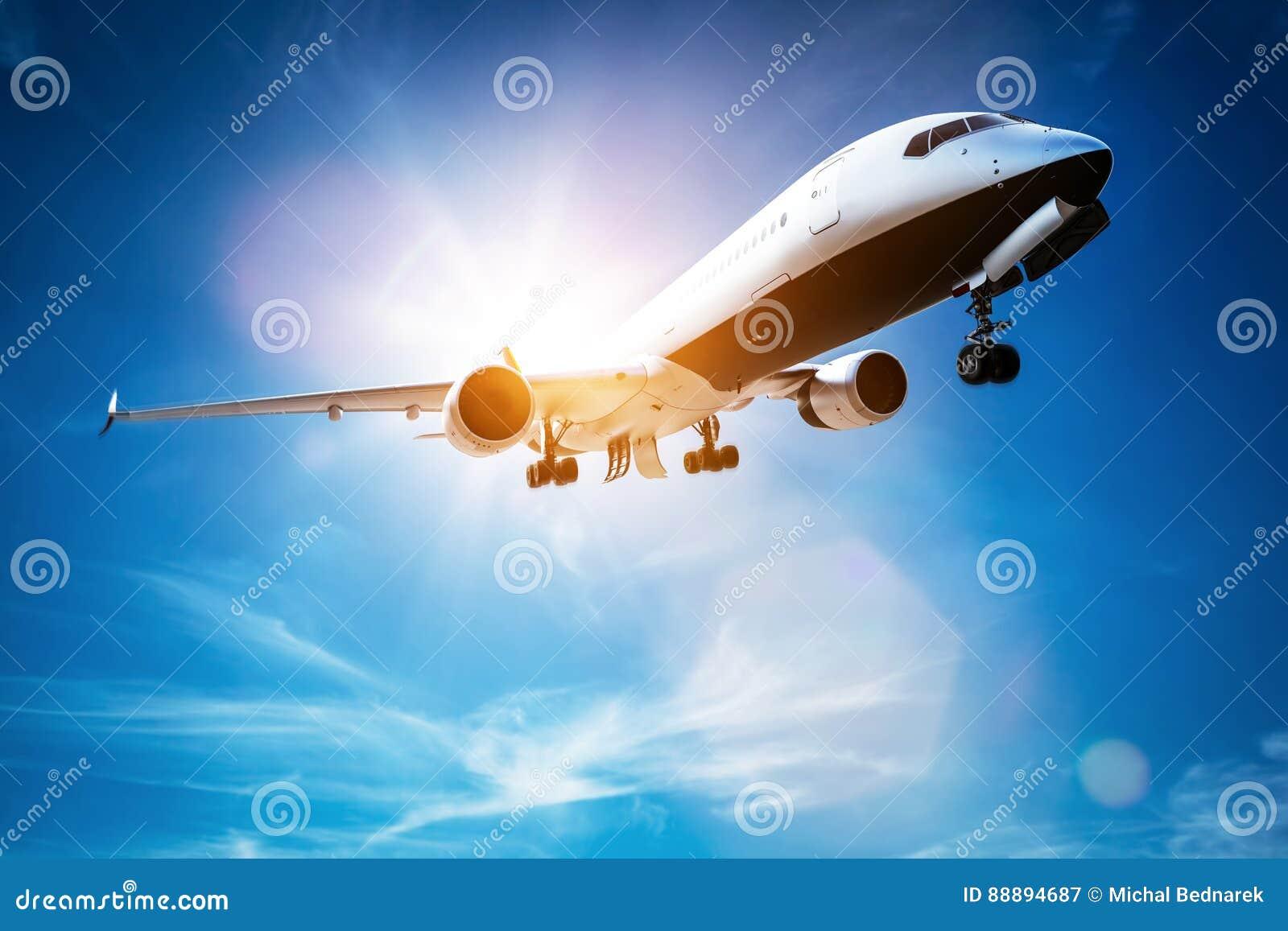 Passenger airplane taking off, sunny blue sky.
