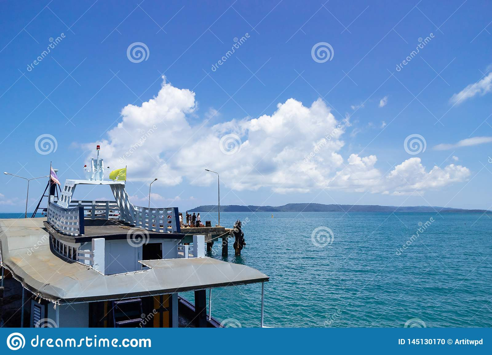 Passenger boat on the left side with big white cloud over the sea in background in summer, Koh Mak Island in Trat, Thailand