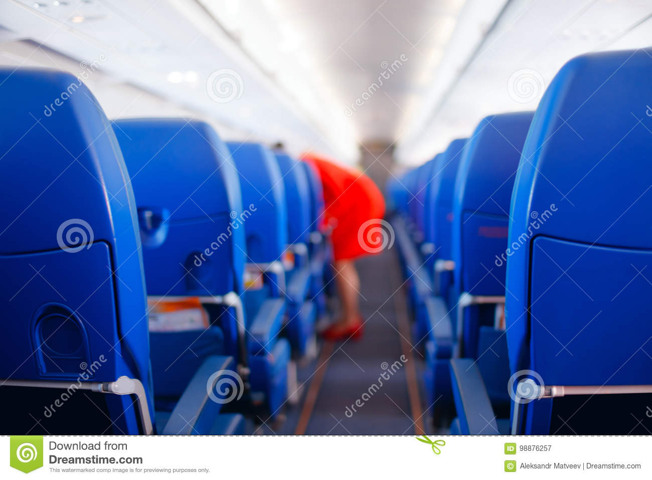 Passenger seat, Interior of airplane with passengers sitting on seats and stewardess walking the aisle in background. stewardess s