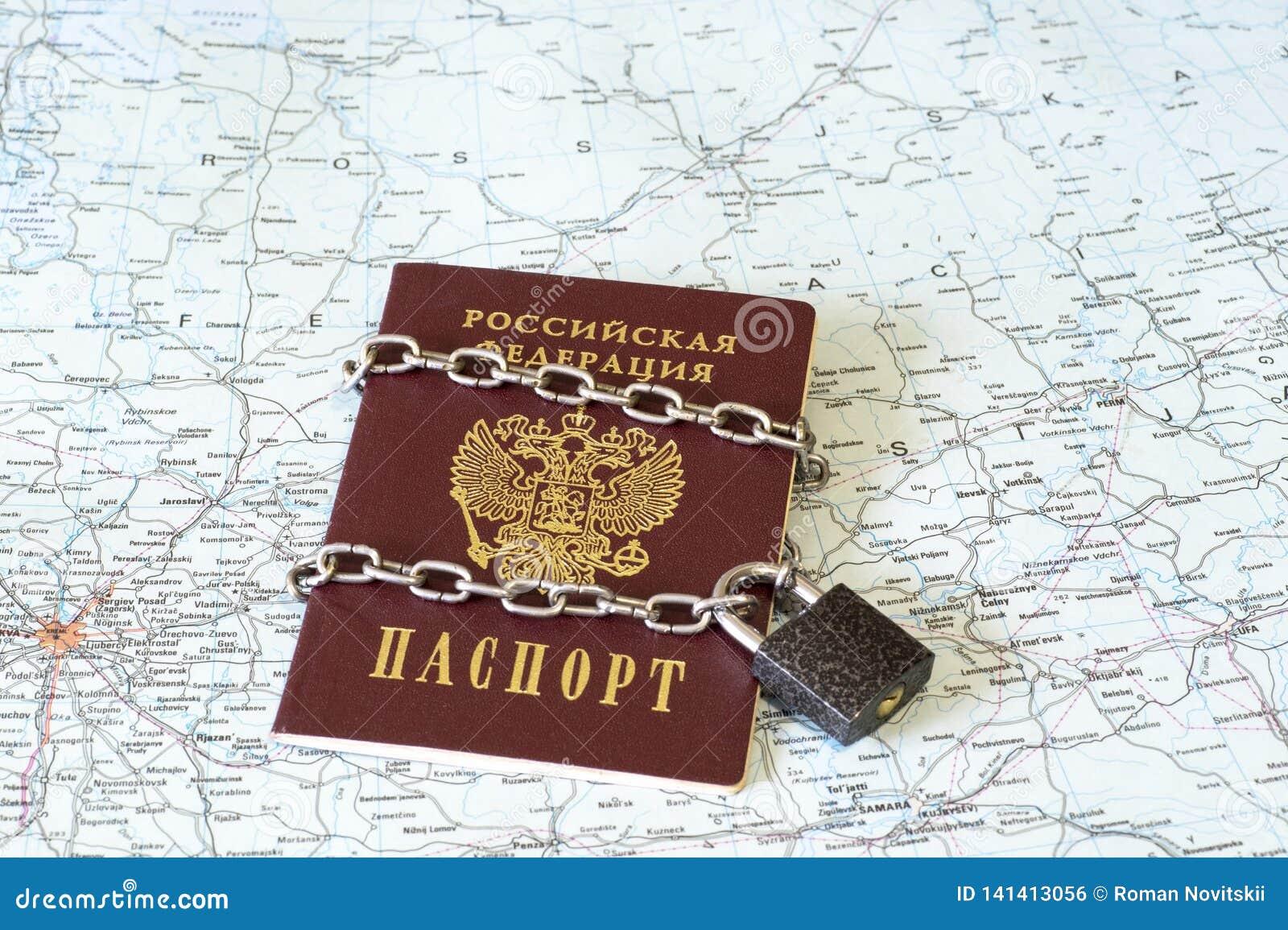 Passeport d un citoyen de la Fédération de Russie dans une chaîne en métal sur la serrure sur le fond de la carte géographique de