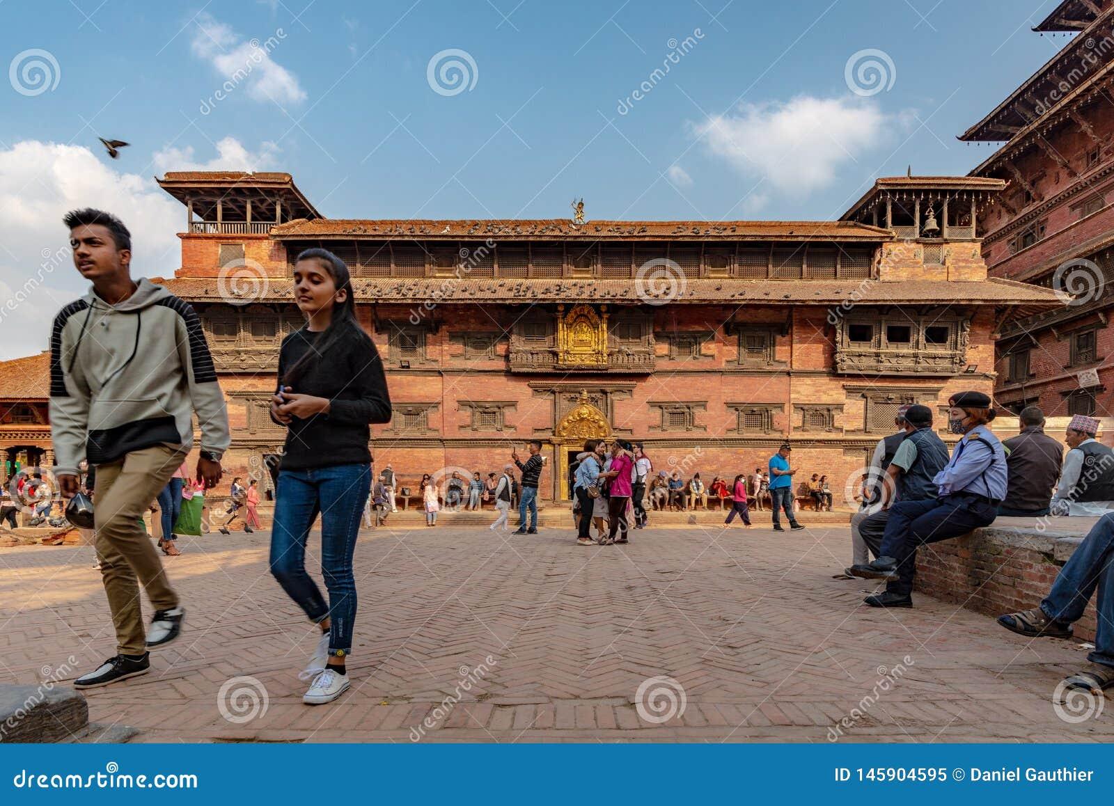 Passersby och huvudbyggnaden av Royal Palace av Patan