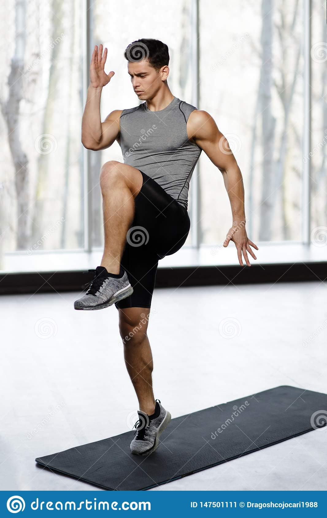 Passform idrotts- manlig modell i sportswearen som gör styrkaövning med knäet upp i idrottshallen som isoleras på en stor fönster