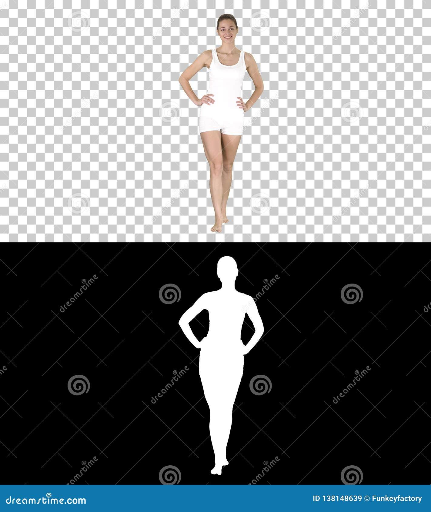 Passform och sportig flicka i den vita underkläderna som barfota går med händer på hennes höfter, Alpha Channel