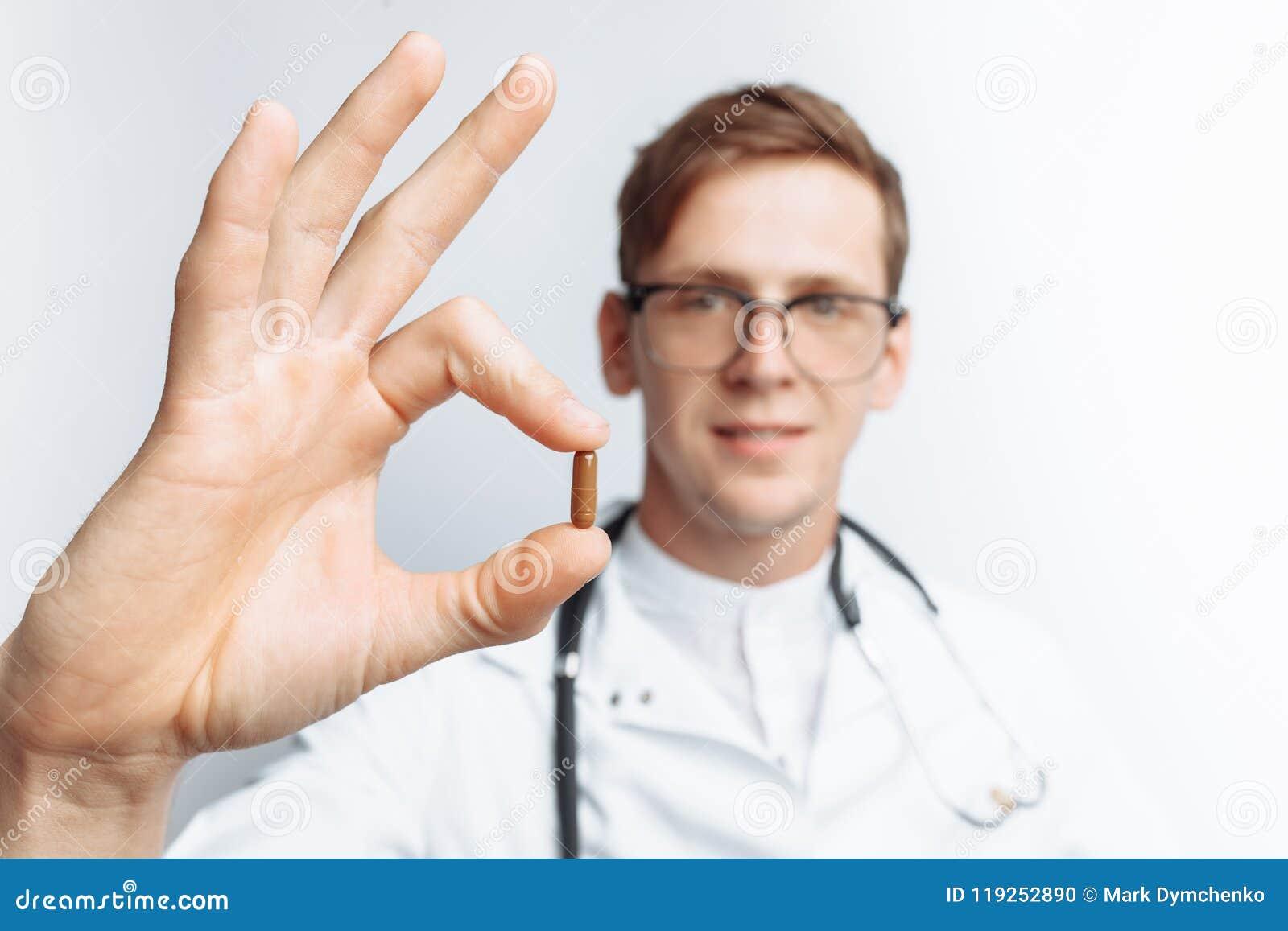 Passi la compressa della tenuta di medico, il primo piano, fondo bianco, per la pubblicità, inserzione del testo