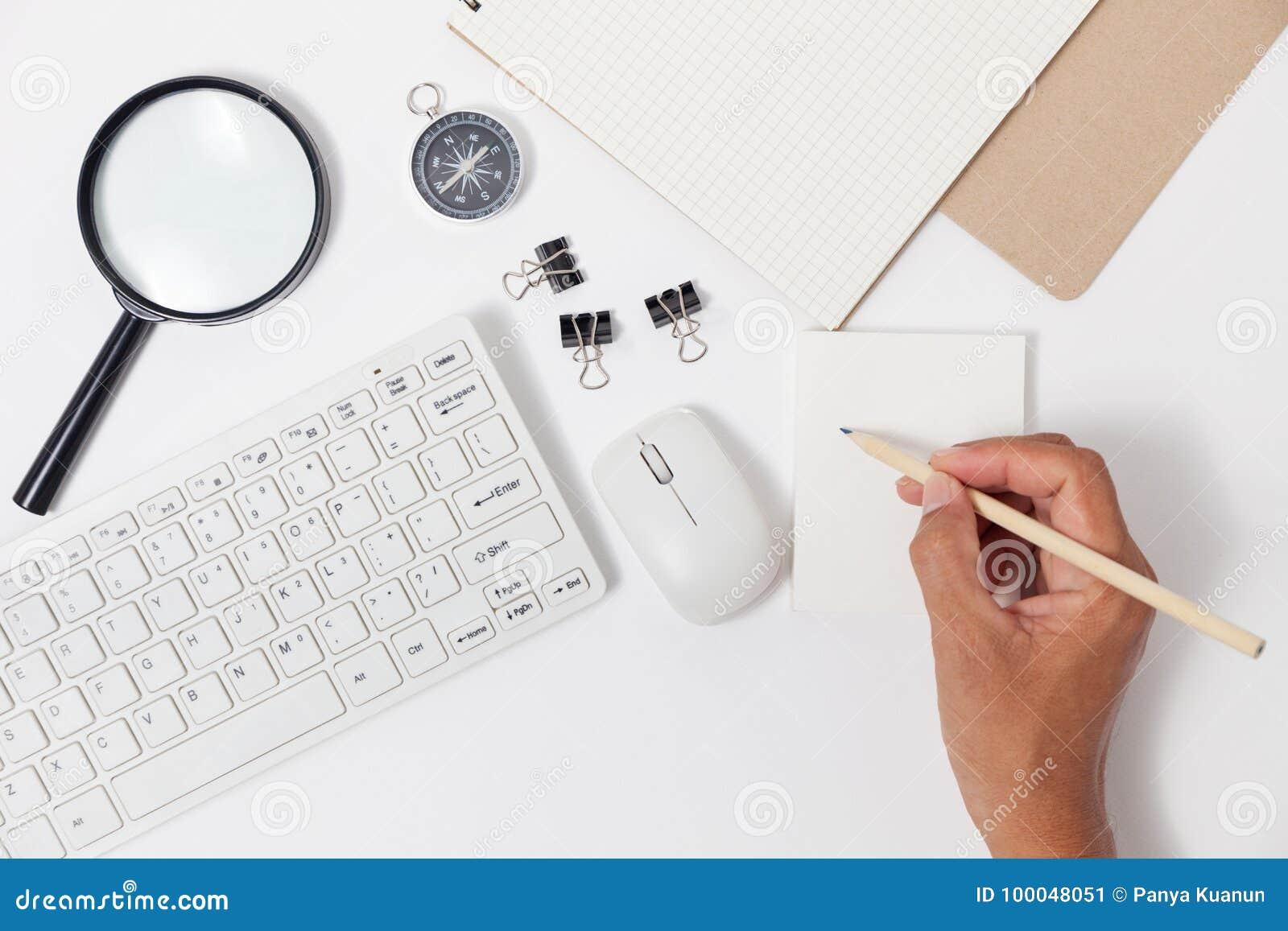 Passi la scrittura della matita di uso sulla nota e sugli oggetti business del Libro Bianco