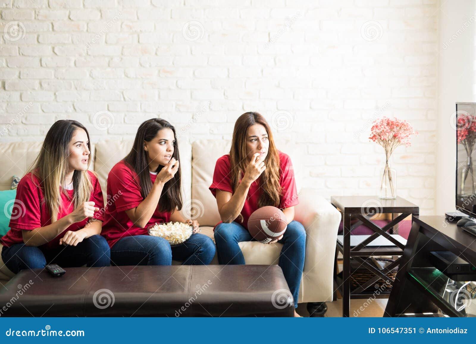 Passionés du football observant un jeu à la TV
