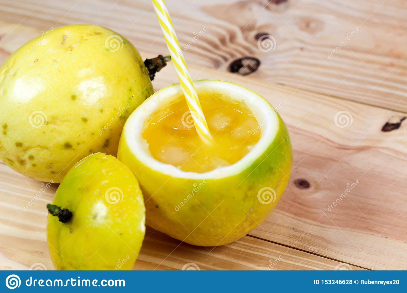 Passion fruits half and juice on the vintage wooden background