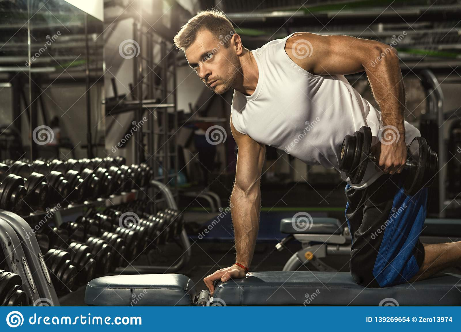 0b9c94f69028 Handsome young muscular athletic man exercising at the gym weightlifting  doing triceps deadlift exercise with dumbbells copyspace motivation  lifestyle ...
