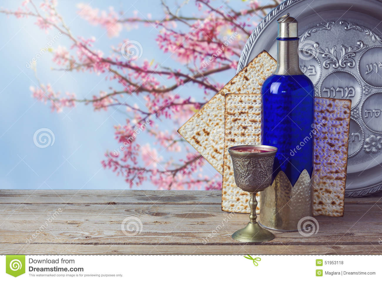 Passover matzo and wine on wooden vintage table over blossom tree background.