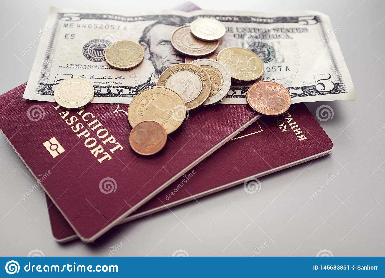 Passport with banknotes and coins on a simple background. business, tourism, travel concept