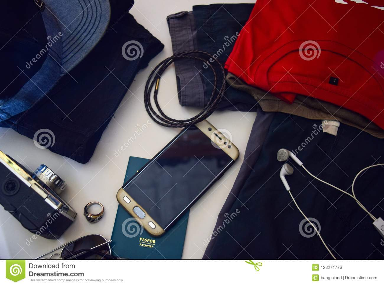 Passport, sunglasses, old camera, jeans, shirt, bracelet and sunglasses are lying on white background. Preparing for traveling