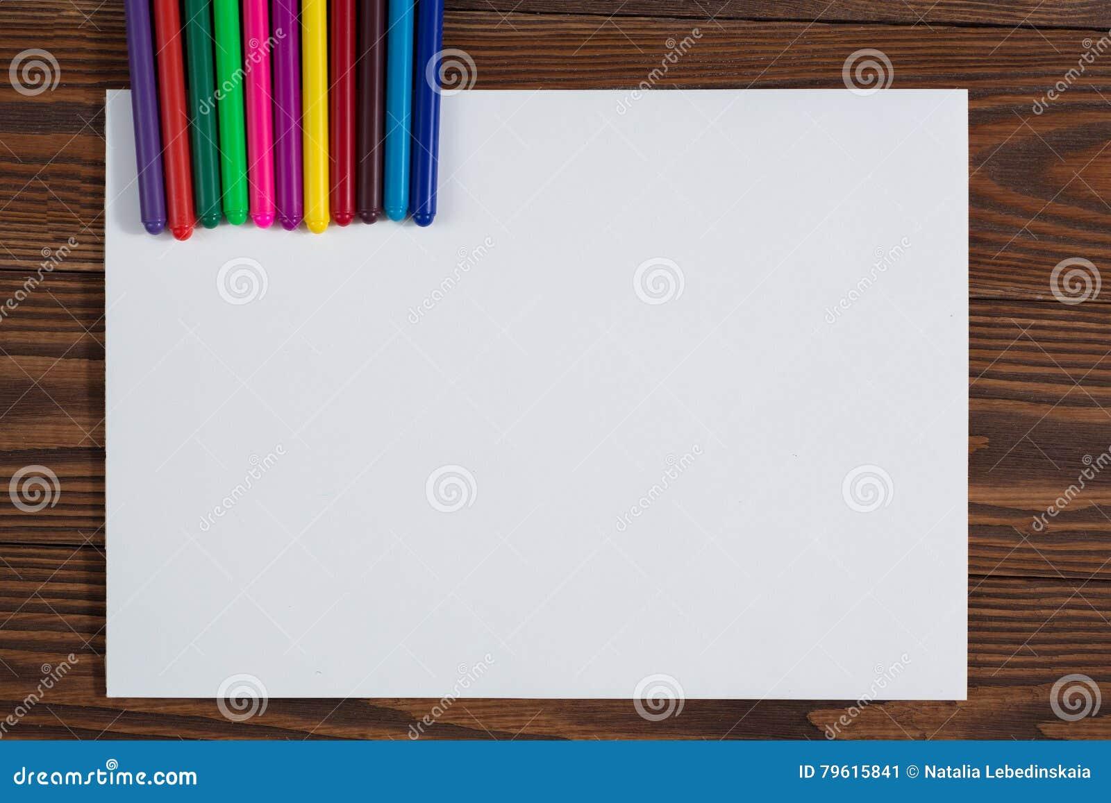 Pastéis coloridos e uma folha de papel a madeira do caderno