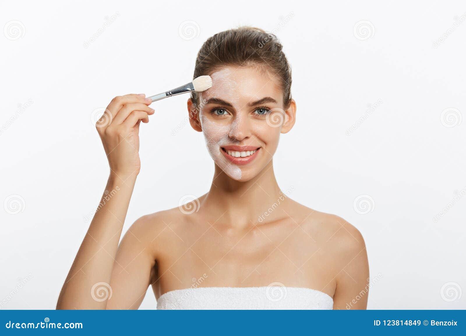 Past de portret mooie naakte vrouw kosmetisch wit kleimasker met borstel toe Geïsoleerd op een witte achtergrond Concept van