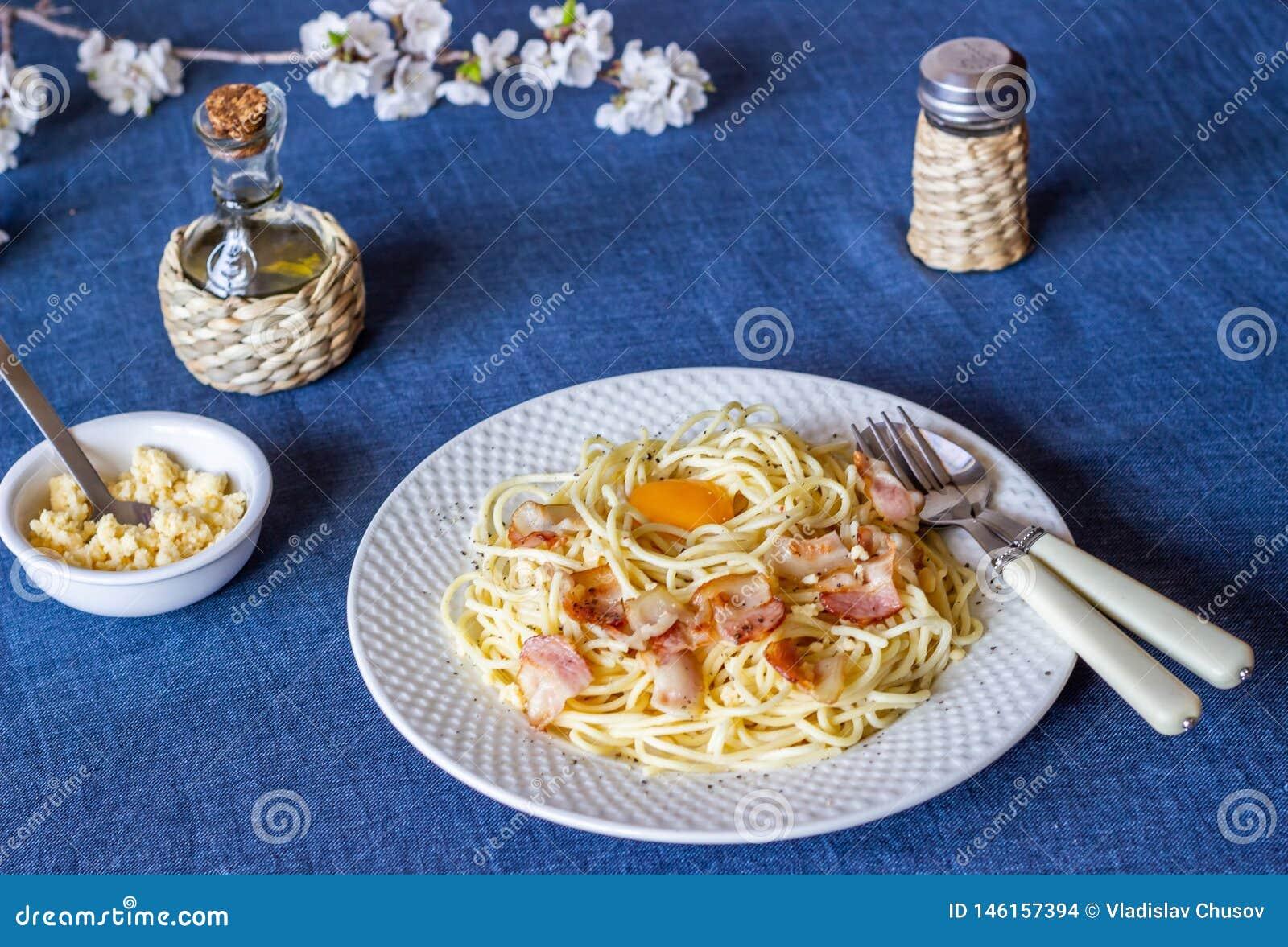 Pasta Carbonara. Flowers in the background. Italian food