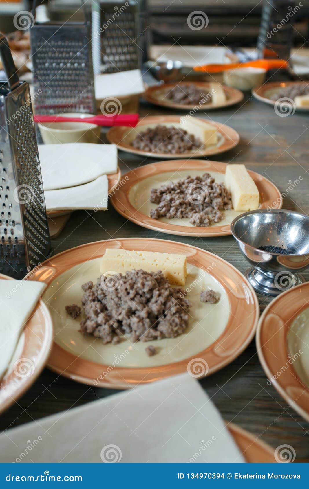 Pasta, carne tajada frita y utensilios para las clases de cocina en la tabla de madera, concepto de clase de cocina