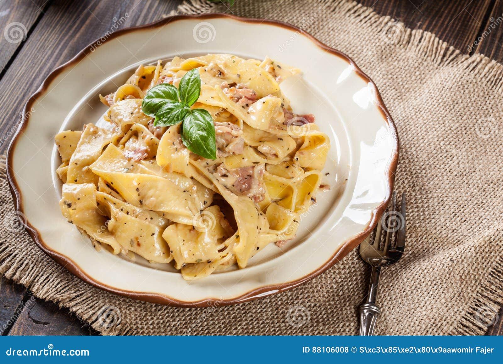 Pasta di Pappardelle con la salsa di formaggio e di prosciutto di Parma su un piatto