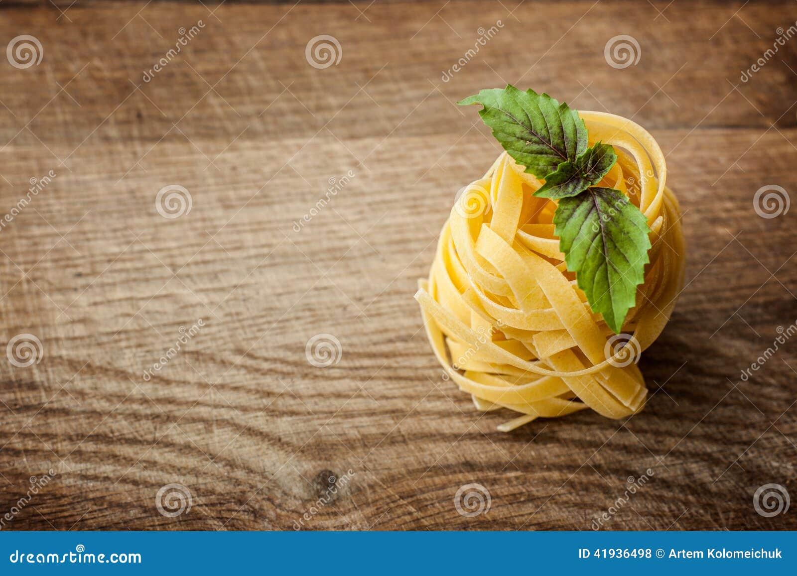 Pasta fresh basil on wood