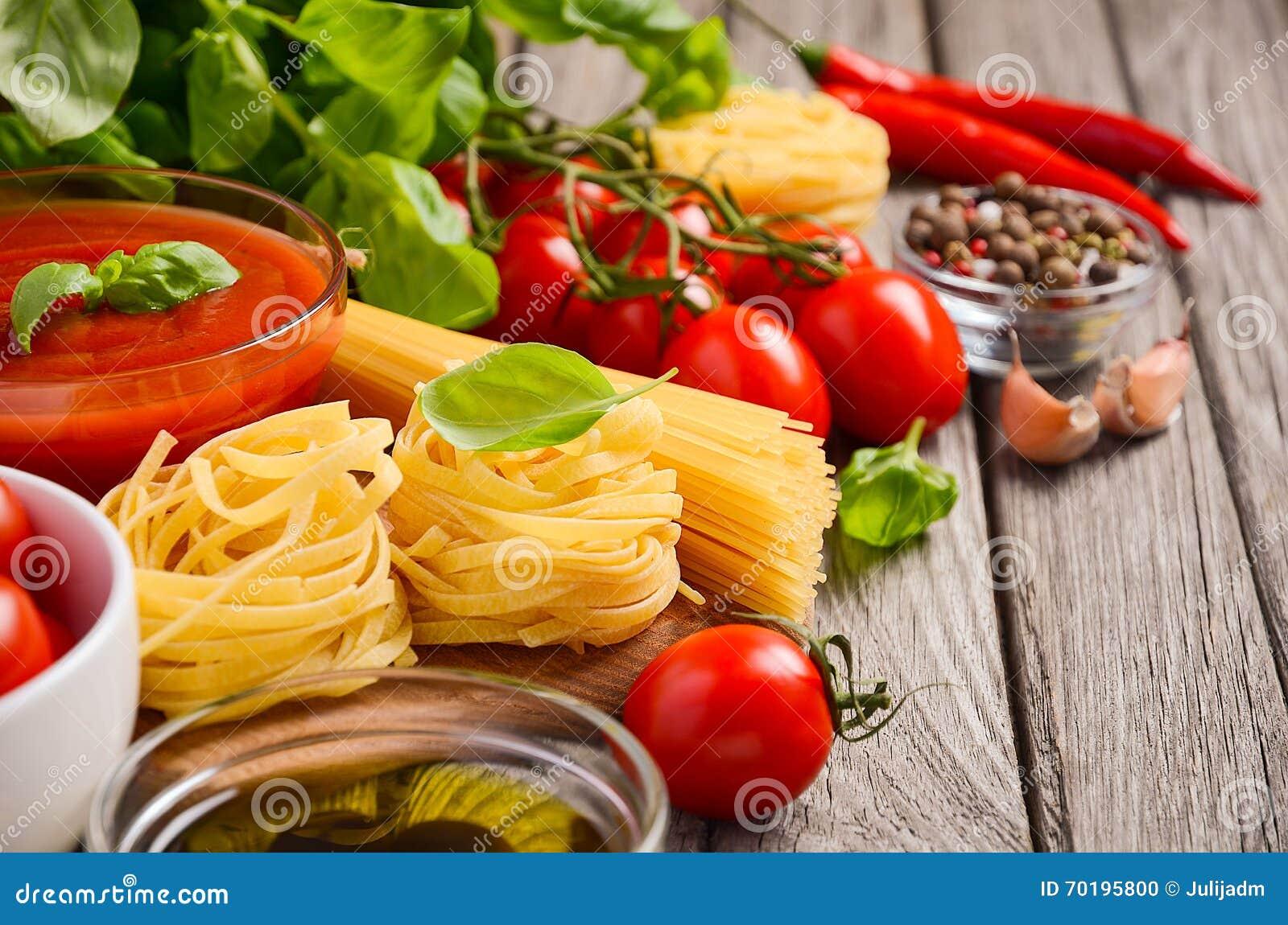 Pasta, grönsaker, örter och kryddor för italiensk mat på den lantliga trätabellen
