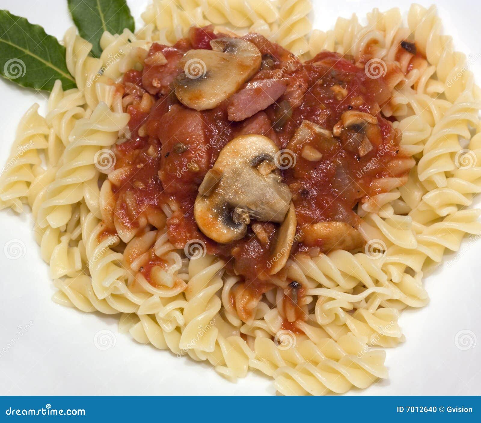 Fusilli pasta with mushrooms and bacon in tomato sauce.