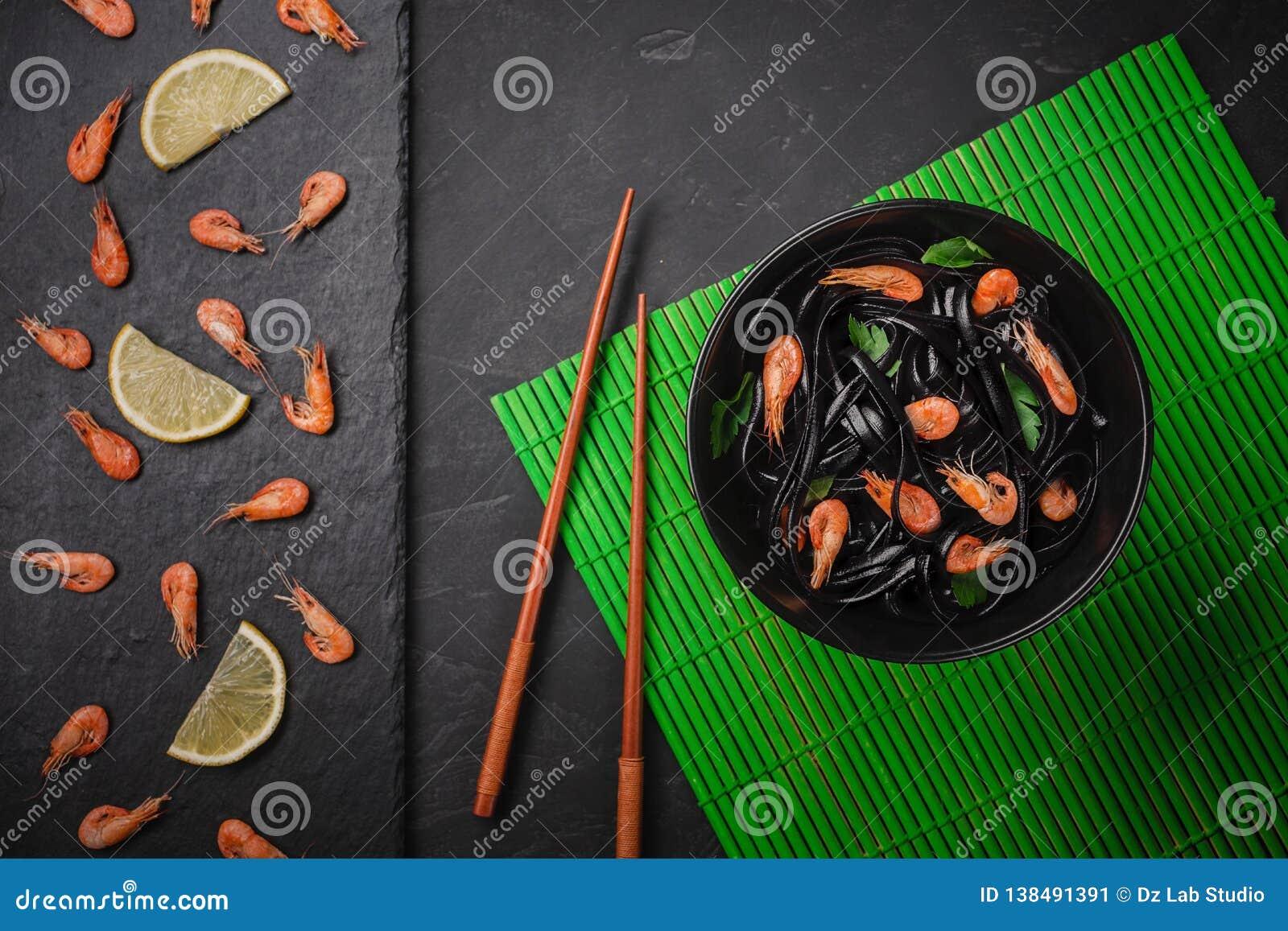 Pasta nera del Fettuccine dell inchiostro del calamaro con i gamberetti o gamberetti, prezzemolo, peperoncino rosso in vino e sal