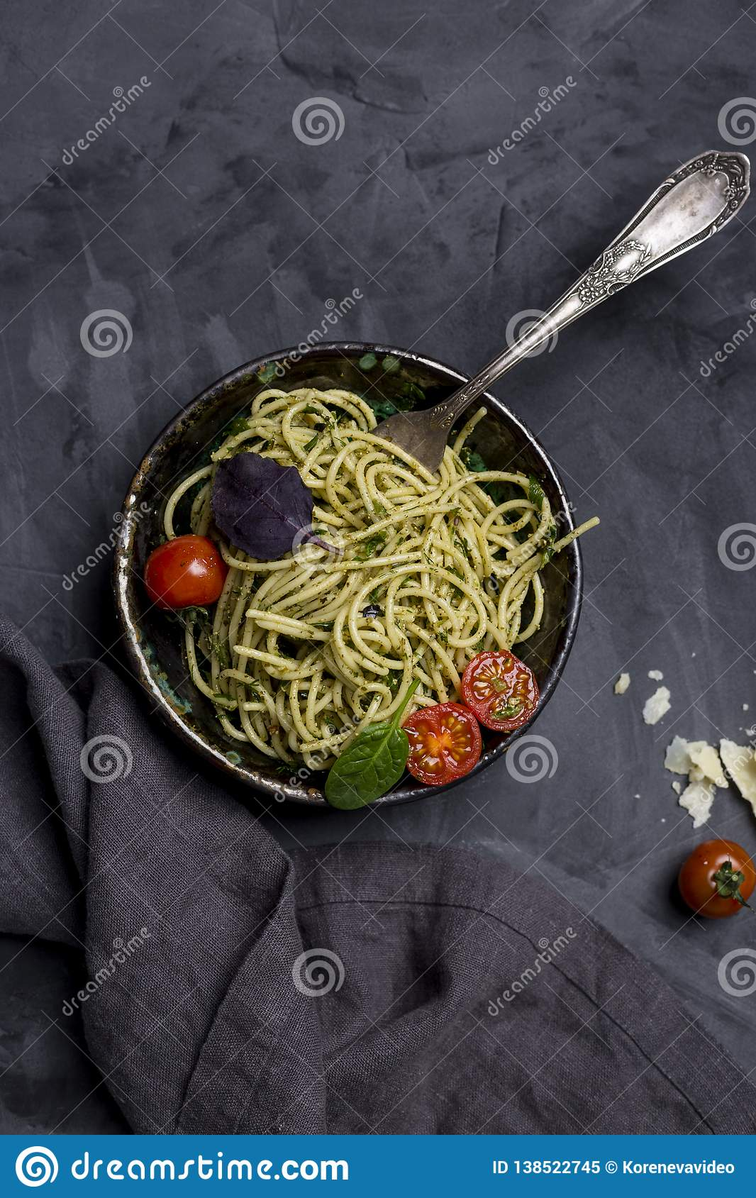 Pasta with pesto in bowl at dark background
