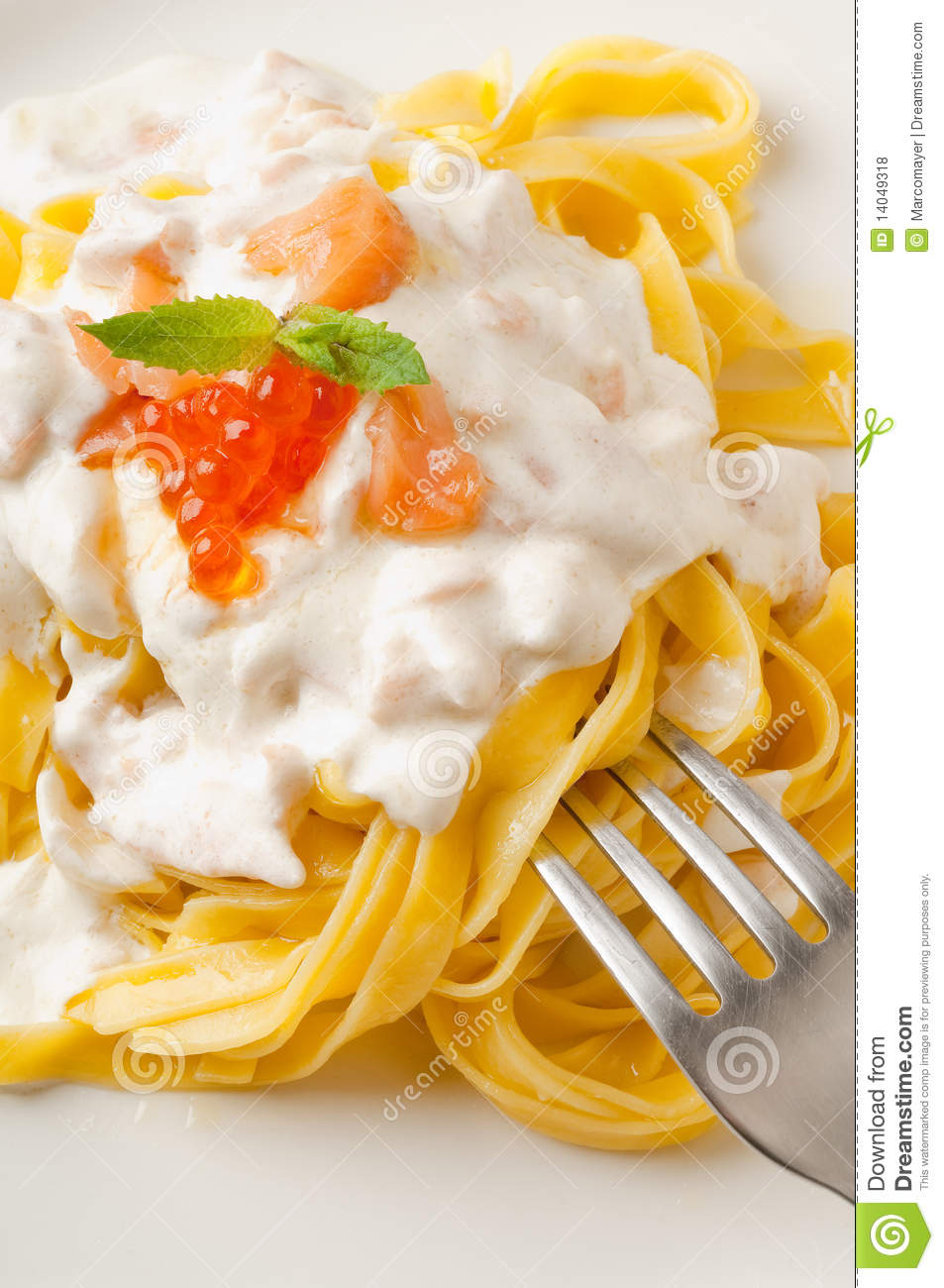 Pasta with smoked salmon, cream sauce and salmon eggs with fork close ...
