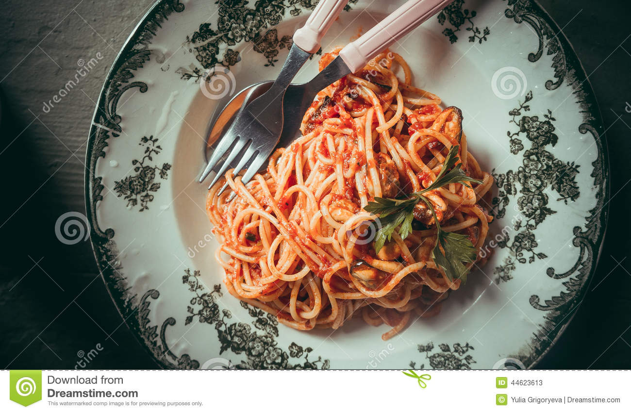 Spaghetti pasta with tomato sauce, mussels and cheese parmesan. Toned ...