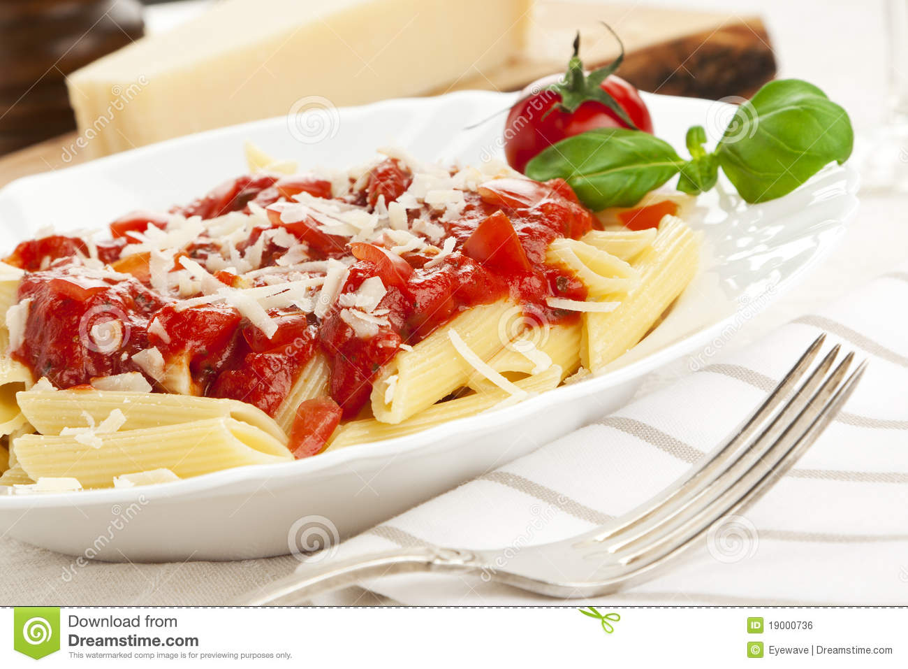 Penne with tomato sauce and grated cheese, garnished with tomato and ...