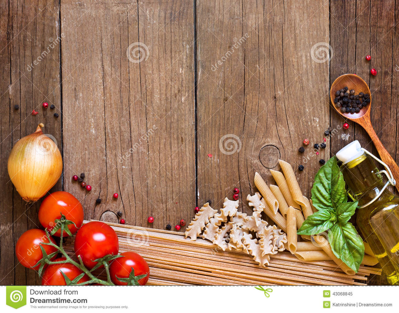 Pasta, tomatoes, onion, olive oil and basil on wooden background