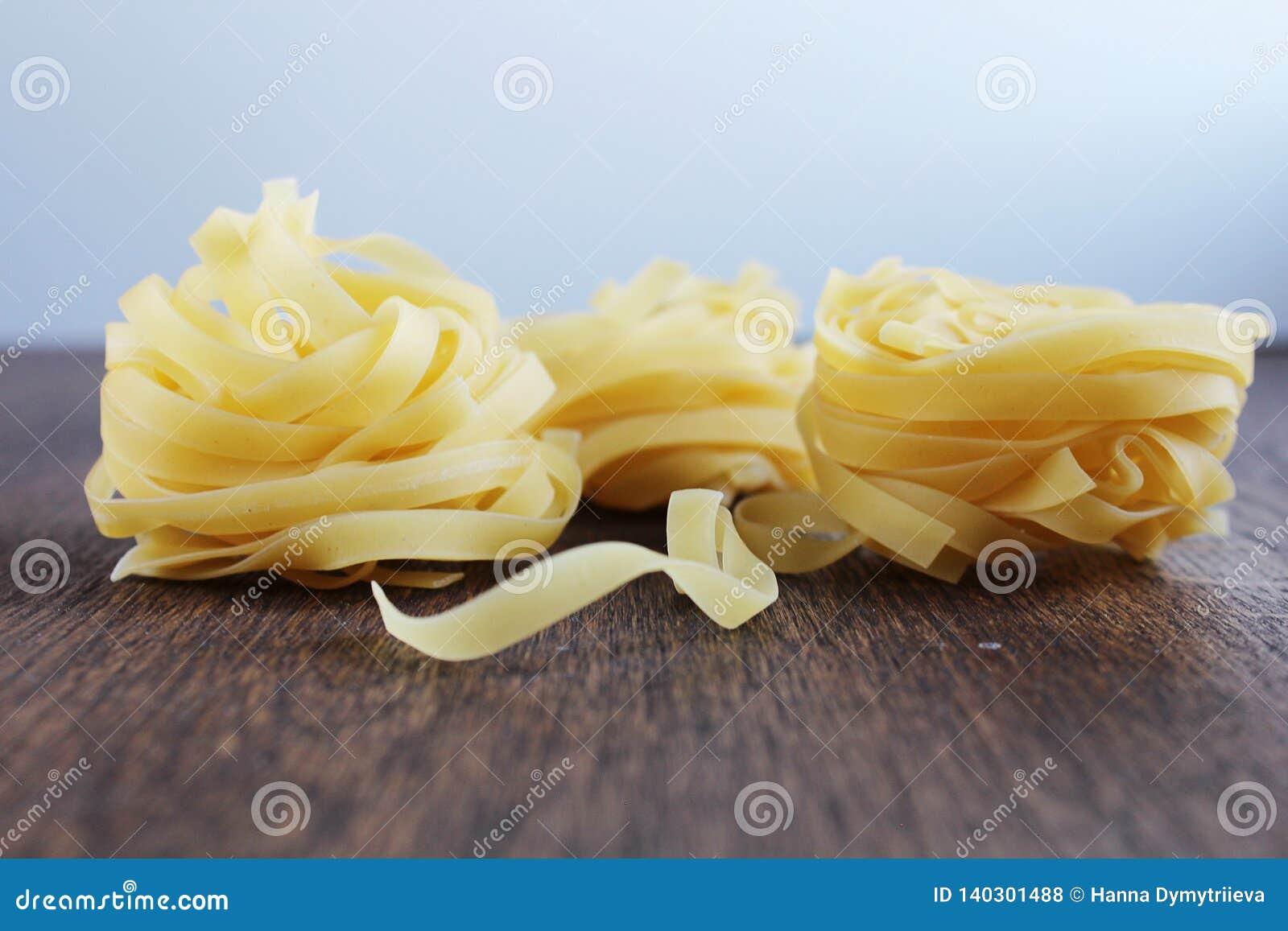 Pastas amarillas tres en la tabla de madera