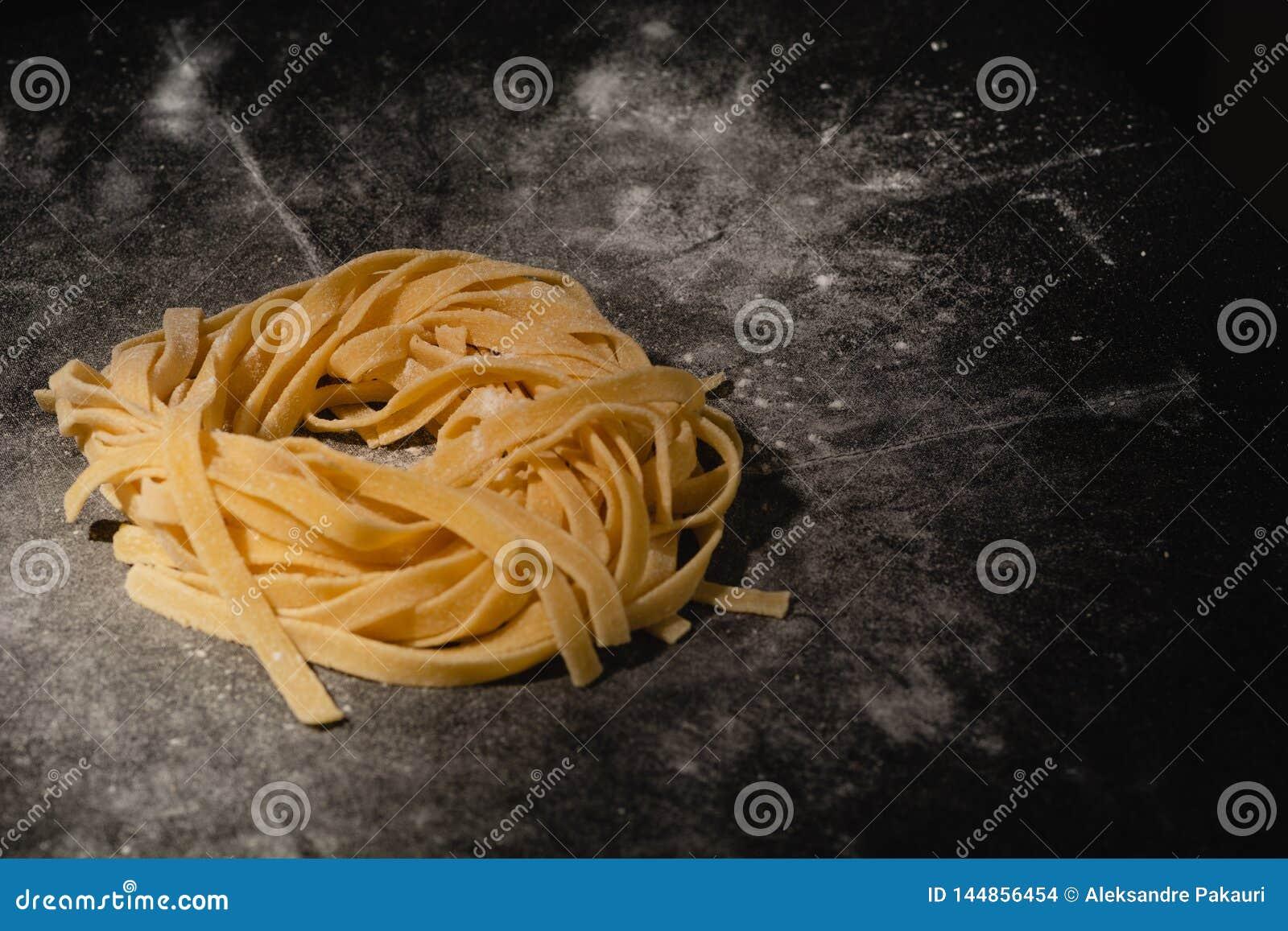 Pastas crudas aisladas en un fondo negro con un lugar para el texto Pastas italianas tradicionales, tallarines, tallarines Visi?n