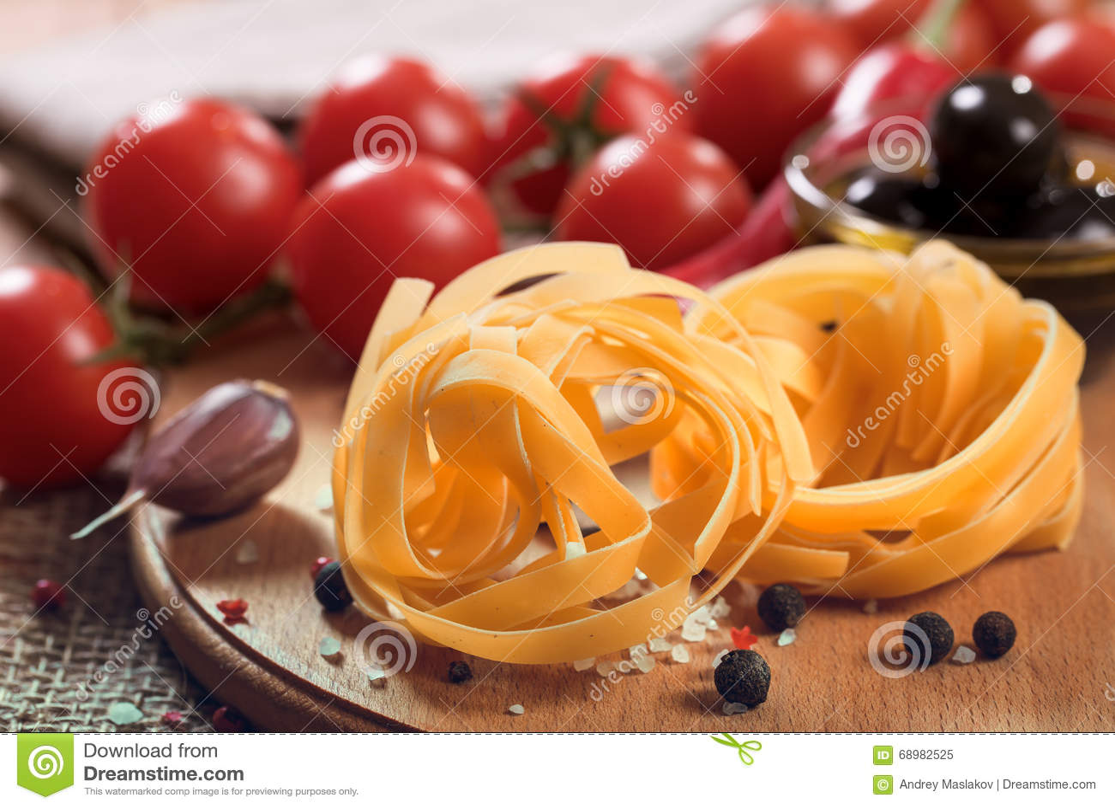 Pastas crudas del fettuccine en el tablero de madera