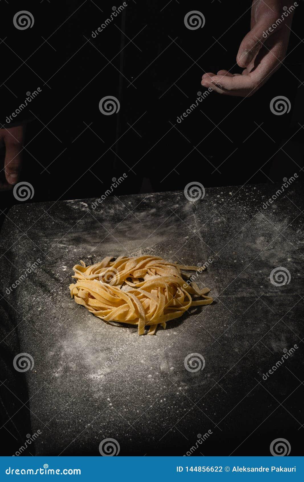 Pastas hechas en casa crudas italianas frescas Manos que hacen las pastas Espaguetis Espaguetis italianos frescos Primer del proc